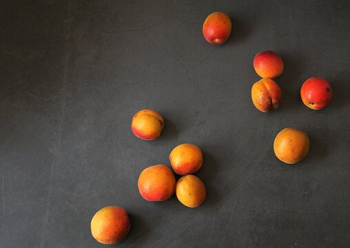 fresh apricots, orange fruits, summer vitamins, small apricots on a dark background