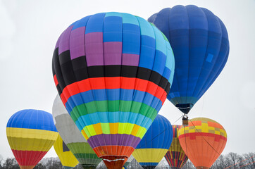 Colourful hot air balloons flying in the sky at the festival aeronautical. Adventure and funny holiday