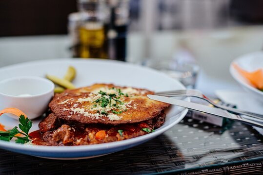 A plate with a dinner dish in a restaurant. Crispy potato pancakes and Hungarian goulash.