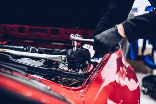 Repairman in car service repairing engine or other car part