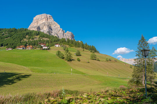 Panoramic view of magical granite Dolomite peaks, alpine pine and spruce forests and green valleys at Colfosco, Corvara at blue sky and sunny day, South Tyrol, Alps, Italy.