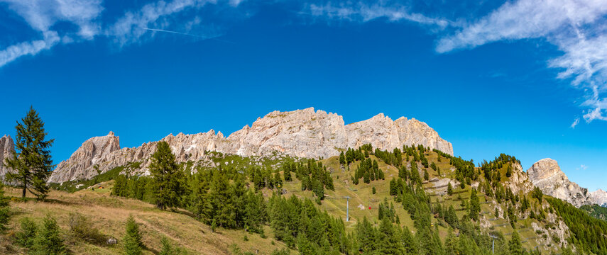 Panoramic view of magical granite Dolomite peaks and alpine forests of Pizes da Cir, Passo Gardena, Colfosco at blue sky and sunny day, South Tyrol, Alps, Italy.