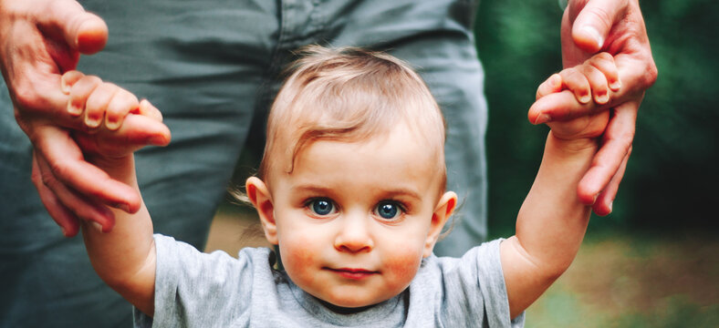 Portrait of a Baby Boy with Blue Eyes in park. trust family hands of child son and father on field outdoor
