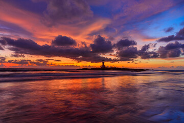 The scenery of the silhouette of Khao Lak Light Beacon in sunset time with the dramatic twilight sky at Nang Thong Beach, Phang Nga, Thailand.