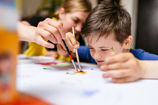 Young female teacher explain, talk at desk with a down syndrome schoolboy. Color painting for disabled kids, child who are down syndrome and student teacher, development of children with spesial needs