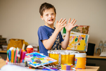 Young Caucasian Boy with Down Syndrome Concentrating On Her Hand Clapping Game in Home or Art Class...