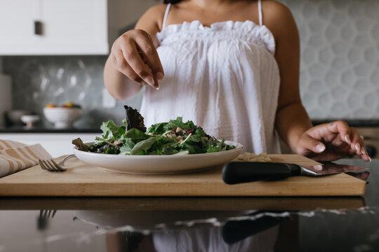 Woman preparing salad in luxury kitchen