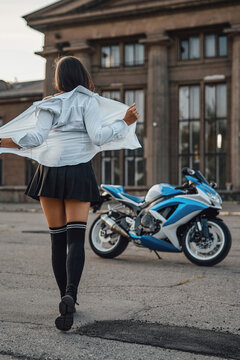 Woman undressing her shirt against motorcycle and building