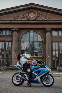 Seductive girl posing on motorcycle smoking vape outside