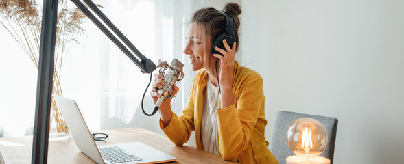 Fototapeta Cheerful woman podcaster recording her voice into microphone. Female radio host streaming podcast using microphone and laptop at his home studio obraz