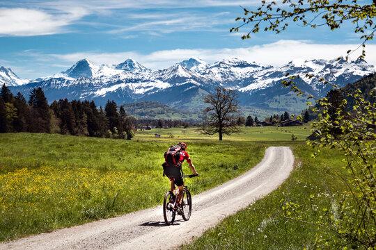 Ein Fahrradfahrer fährt an einem schönen Frühlingstag Richtung berner Alpen, durch das Stockental, berner Oberland, Schweiz. Biken, Radweg, Sport, radfahren, Mann, allein, Landschaft, Alpen.
