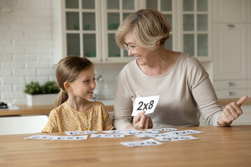 Smiling mature grandmother with little granddaughter learning multiplication table using flash...