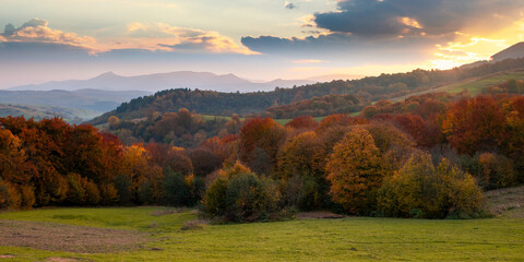 countryside mountain scenery at sunset. beautiful rural landscape in autumn. fields and meadow on rolling hills in evening light. trees in colorful foliage. ridge with high peak in the distance