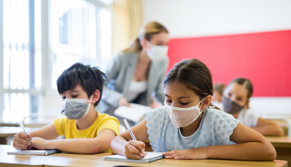 Fototapeta Diligent tween girl in protective mask studying in school with classmates. New life reality in coronavirus pandemic.. obraz