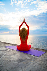 female in a red yoga suit is sitting in lotus pose asana in sun rays near a sea, blue clouds on the horizon