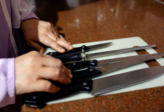 Reem Abd el-Karim, 46, a visually impaired woman touches the knifes in Eman al-Hosseiny's kitchen, the author of the braille cooking book, in Cairo