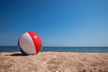 Fototapeta Colorful inflatable ball on sandy beach. Space for text obraz
