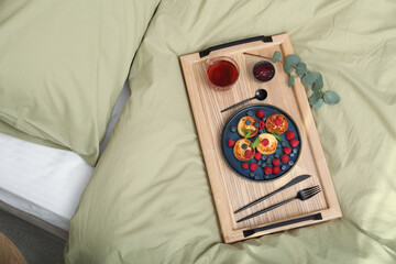 Fototapeta Tasty breakfast served in bedroom. Cottage cheese pancakes with fresh berries and mint on wooden tray, top view obraz