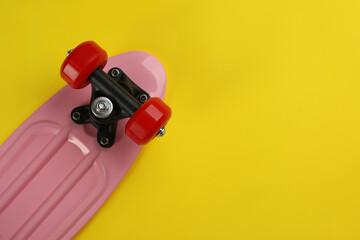 Fototapeta Skateboard on yellow background, top view. Space for text obraz