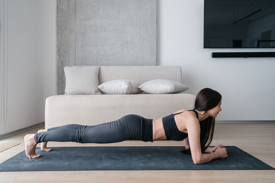 Slim woman standing in plank during training at home