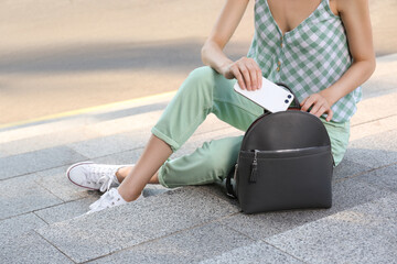 Fototapeta Young woman with stylish backpack and smartphone on stairs outdoors, closeup obraz
