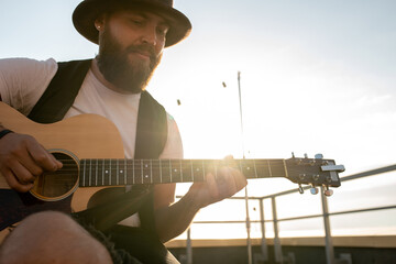 Fototapeta Young bearded man in hat playing guitar on rooftop on sunny day obraz