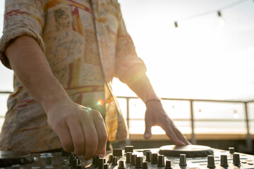 Fototapeta Hand of young man mixing sounds by soundboard at rooftop party obraz