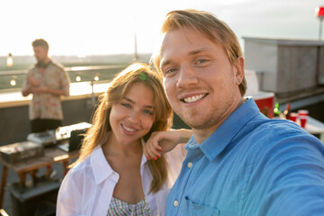 Fototapeta Young smiling couple making selfie in front of camera during rooftop party obraz