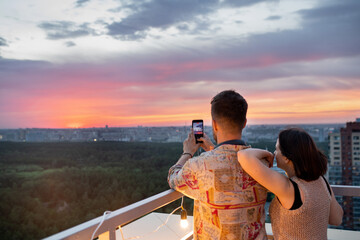 Fototapeta Young man photographing sky during sunset with his girlfriend standing near by on rooftop patio obraz