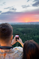 Fototapeta Young man and woman photograpging cloudy sky at sunset in the evening obraz