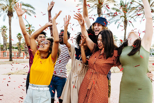 Happy friends throwing confetti and enjoying summer party outdoors - Multiethnic group of young people having fun and celebrating holidays together - Friendship and event celebration concept