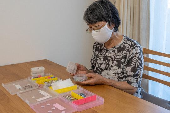 老々介護の家庭の日常。マスクをして糖尿病・高血圧・認知症など複数の薬を事前に容器に分ける