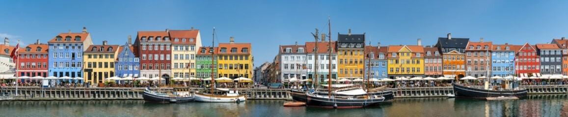 Obraz Panorama view of Nyhawn, the colorful houses next to the old port. Tourist visiting restaurants, cafes and ships in the canal. The most important sightseeing spot in Copenhagen, Denmark. - fototapety do salonu