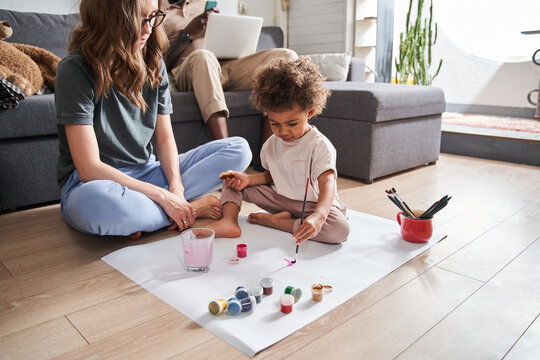 Girl drawing hand made picture with her mother while sitting at the floor together