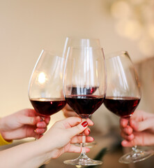 Crop friends clinking glasses of wine