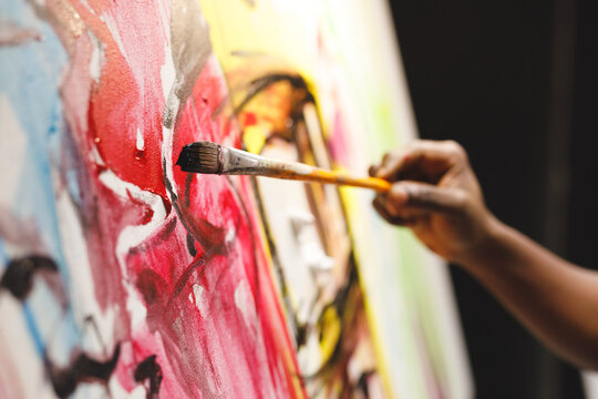 Close up of african american male painter at work painting on canvas in art studio