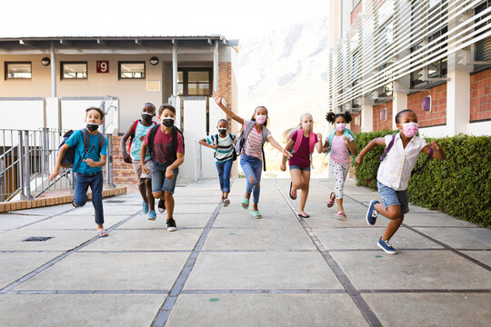 Group of diverse students wearing face masks running at elementary school