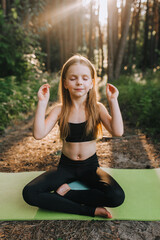 A beautiful blonde preschool girl, a child athlete in a black suit sits on a green rug in the lotus position and meditates, relaxes, performing yoga exercises in the forest in nature.