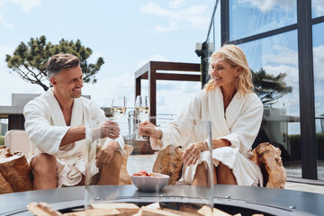 Beautiful mature couple in bathrobes enjoying fruits and champagne while relaxing in luxury hotel outdoors