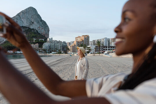 Woman resting on beach near black friend taking photo
