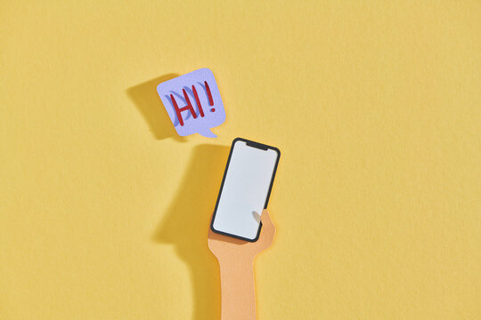 Man hand holding a smart phone with text Hi! on a yellow background