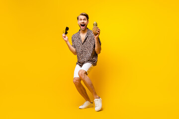 Obraz Full length photo of excited funny gentleman dressed print shirt arm dark glasses pineapple dancing isolated yellow color background - fototapety do salonu