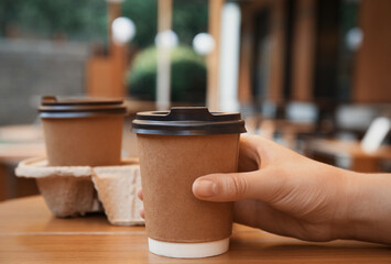 Woman with paper coffee cup at wooden table outdoors, closeup
