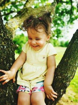Cute Girl Sitting On Tree Trunk