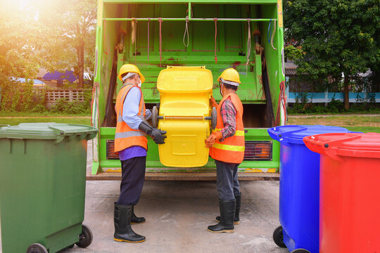 Two dustmen standing by a dustbin lorry emptying wheelie bins, Thailand