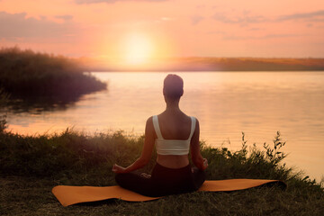 Woman meditating near river in twilight, back view