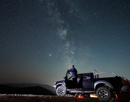 Rear view of young man who enjoying magic Milky Way and many stars in night sky looking out of the cabin black SUV car. Night riding on stony mountain roads by big car.