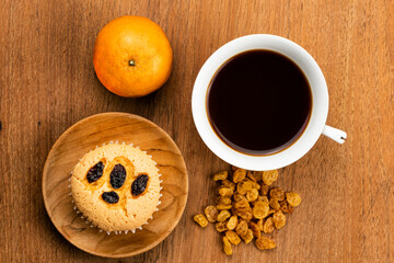 Fototapete - Top view of homemade raisin sponge cupcake in wooden plate.