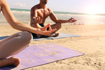 Close up hand gesture doing yoga with lotus position on summer beach, practicing meditation in nature at seashore of tropical ocean blue sea, sport people doing exercise, training workout outdoor