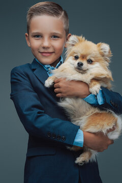 Little boy with fluffy dog posing against gray background